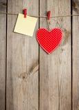 Coeur rouge et carte accrochant sur la corde à linge pour Valentine Day Photographie stock