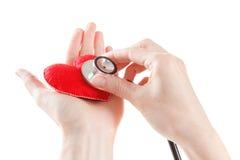 Coeur rouge et un stéthoscope sur le fond blanc Image stock
