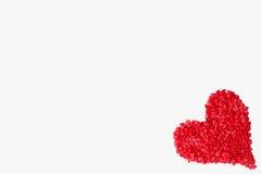 Coeur rouge fait de beaucoup de petits coeurs dans le coin sur un fond blanc Photographie stock libre de droits