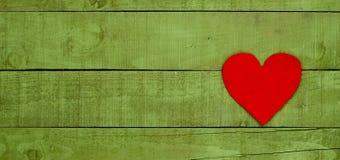 Coeur rouge fait de feutre sur le fond en bois vert Photographie stock libre de droits