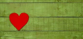 Coeur rouge fait de feutre sur le fond en bois vert Image stock