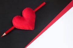 Coeur rouge fait de feutre sur un fond noir Photographie stock libre de droits