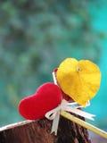 Coeur rouge fait de serviette, bâton avec le crayon, ruban de lien et feuilles jaunes en forme de coeur dans un verre avec les gr Photo stock