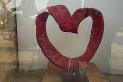 Coeur rouge fait en ruban en métal sur un fond d'un mur blanc, le symbole de l'amour et la valentine Photographie stock libre de droits