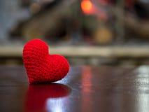 Coeur rouge fait main de fil sur la table en bois dans la cheminée avant le coeur rouge à gauche de la photo et le fond copient l Photo libre de droits