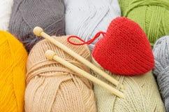 Coeur rouge fait main et écheveaux de fil pour le tricotage Le concept du confort et de l'amour Photos stock