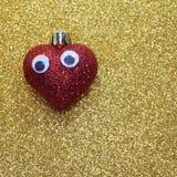 Coeur rouge isolé avec de grands yeux sur le fond d'or brillant Photographie stock libre de droits