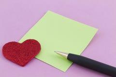 Coeur rouge, note verte, et stylo sur le fond rose Photographie stock libre de droits