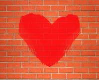 Coeur rouge peint sur le fond orange de mur de briques Images libres de droits