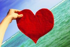 Coeur rouge senti sur le fond du ciel et de la mer Photographie stock