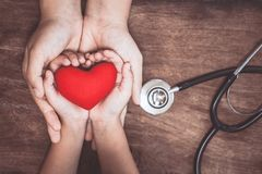 Coeur rouge sur des mains de femme et d'enfant et avec le stéthoscope du ` s de docteur Photos libres de droits