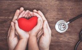 Coeur rouge sur des mains de femme et d'enfant et avec le stéthoscope du ` s de docteur Image libre de droits