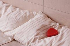 Coeur rouge sur l'oreiller. Symbole d'amour et de romance. Photos stock