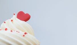 Coeur rouge sur la crème de petit gâteau Images libres de droits
