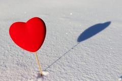 Coeur rouge sur la neige avec l'ombre Photographie stock libre de droits