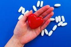 Coeur rouge sur la paume femelle sur un fond bleu avec les pilules blanches photo libre de droits