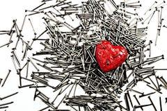 Coeur rouge sur la pile des clous de fer, percée par trois clous Photographie stock libre de droits
