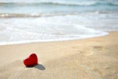 Coeur rouge sur la plage de mer - l'amour détendent le concept Photographie stock libre de droits