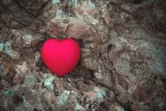 Coeur rouge sur la roche Images stock