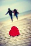 Coeur rouge sur la route avec l'homme et la femme sur le fond Photos stock