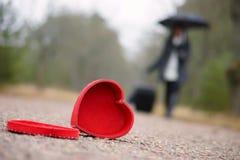 Coeur rouge sur la route et la femme avec le bagage et le parapluie Photographie stock libre de droits
