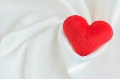 Coeur rouge sur le fond blanc de textile de satin Photographie stock libre de droits