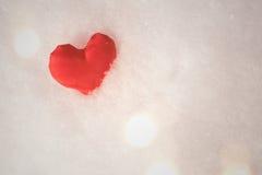 Coeur rouge sur le fond de neige Photos stock