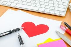 Coeur rouge sur le livre blanc avec le stylo sur le bureau d'ordinateur Photo stock