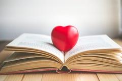Coeur rouge sur le livre ouvert avec l'espace de copie dans la relaxation et le MOIS confortable Images stock