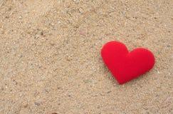 Coeur rouge sur le plancher de sable, concept d'amour Image stock