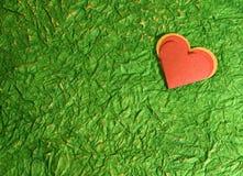Coeur rouge sur le vert Photographie stock