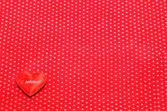 Coeur rouge sur un fond de tissu rouge Photo stock