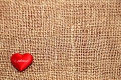 Coeur rouge sur un fond de toile de jute Photos libres de droits