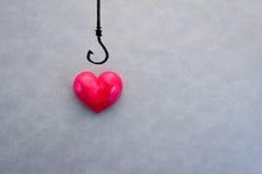 Coeur rouge sur un hameçon Photos stock