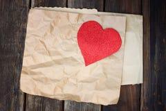 Coeur rouge sur un papier brun chiffonné sur le fond en bois Images libres de droits