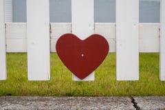 Coeur rouge sur une barrière Photos stock