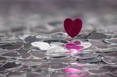 Coeur rouge sur une pile de coeurs argentés Photographie stock libre de droits
