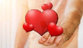 Coeur rouge tiré par la main émouvant de jeune homme Image stock