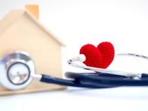 Coeur rouge utilisant le stéthoscope sur le fond bleu pour le contrôle de santé de maison Concept de l'amour et de la maison pati Image stock