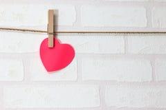 Coeur rouge vide au-dessus de papier peint de brique Images stock