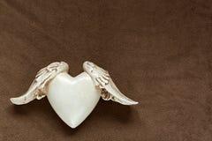 Coeur rustique blanc avec des ailes sur le tissu brun mou d'ouatine Conce Images libres de droits