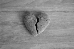 Coeur sablé cassé sur le fond en bois noir et blanc en tant que fond malheureux d'amour Photo stock