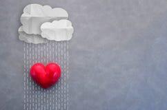 Coeur se tenant sous le concept nuageux d'amour de pluie Photos stock
