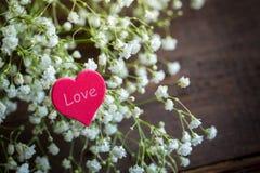 Coeur se trouvant sur un bouquet des fleurs Photo libre de droits