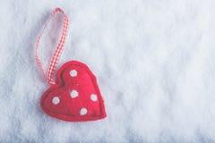 Coeur suave de jouet rouge sur un fond blanc givré de neige Concept d'amour et de St Valentine Images stock