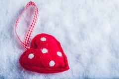 Coeur suave de jouet rouge sur un fond blanc givré de neige Concept d'amour et de St Valentine Photos stock