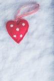 Coeur suave de jouet rouge sur un fond blanc givré de neige Concept d'amour et de St Valentine Images libres de droits