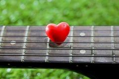 Coeur sur des guitares de cou et ficelles sur l'herbe Photos stock