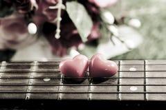 Coeur sur des guitares de cou et ficelles sur l'herbe Image stock