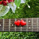Coeur sur des guitares de cou et ficelles sur l'herbe Image libre de droits
